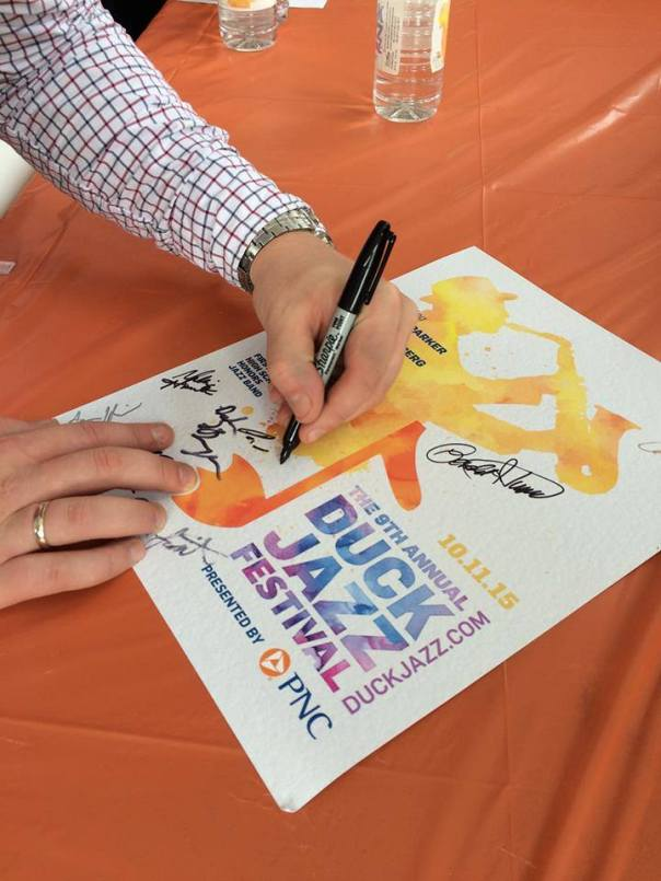 Our trumpeter Paul Rogers signs a Duck Jazz Festival poster, featuring the silhouette of Maceo Parker, the festival headliner.